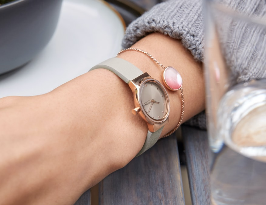 Homme au style minimaliste portant une montre Skagen avec un bracelet en cuir brun. Femme au style minimaliste portant une montre Skagen avec un bracelet en cuir brun.