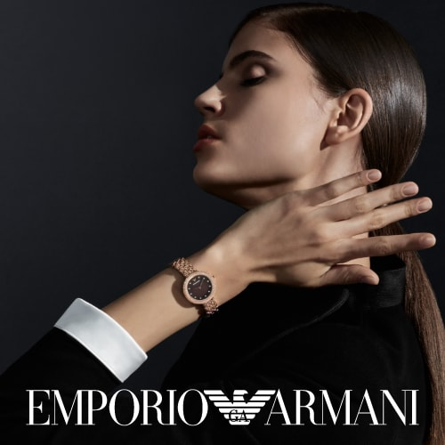 Modern woman wearing Emporio Armani watch in rose gold-tone with a glitz topring and brown dial.