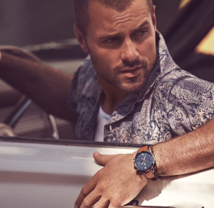 Stylish man and woman driving car wearing gold and silver-tone ladies watch and brown leather men's watch with a blue dial.