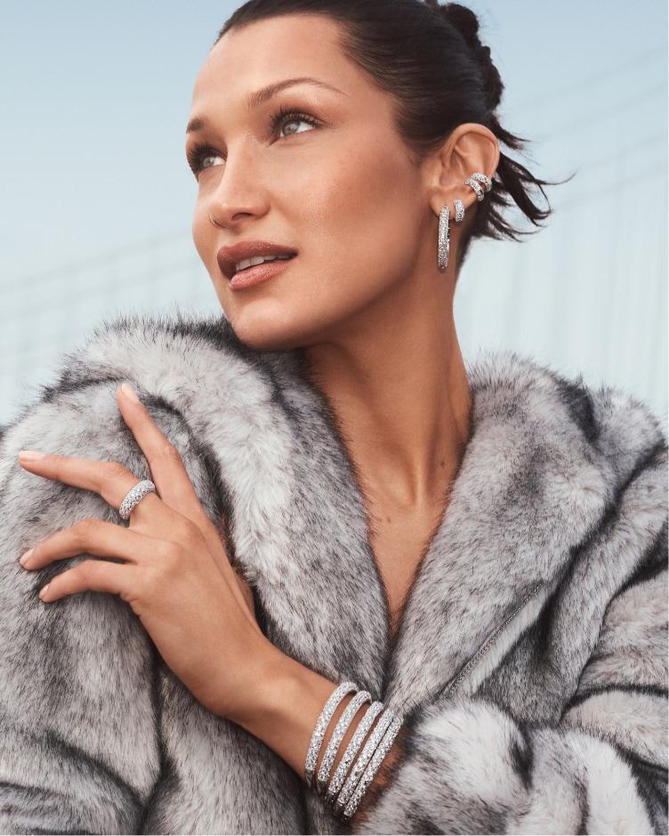 High-fashion woman wearing Michael Kors' stingray-pavé silver-tone ring, bracelets and hoop earrings.