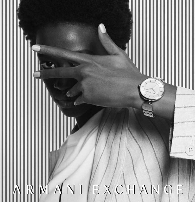 Modern, stylish man and woman wearing black and white A|X watches.