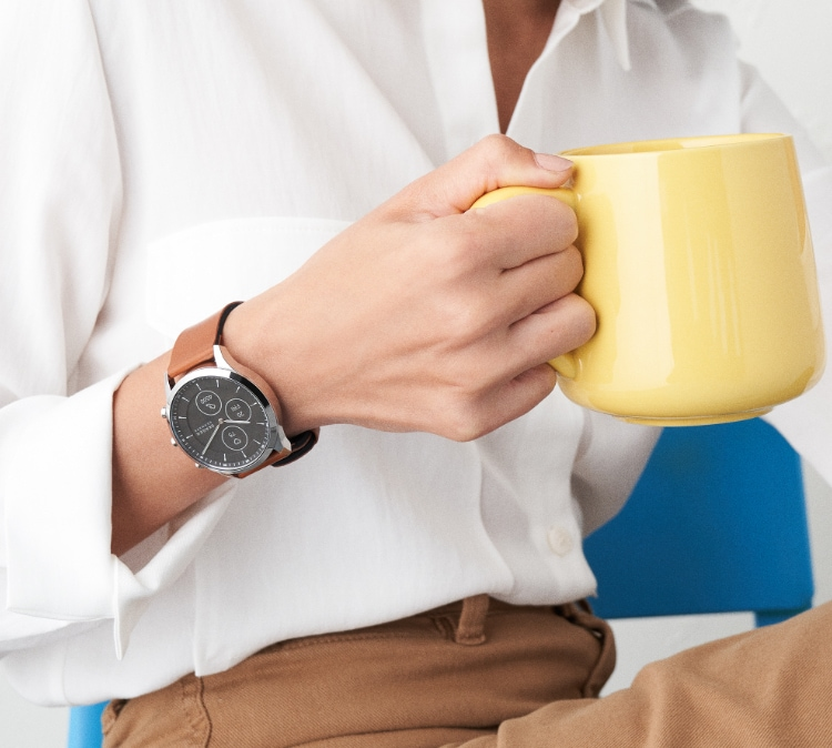 Minimalist style man wearing Skagen watch featuring brown leather strap. Minimalist style woman wearing Skagen watch featuring brown leather strap.