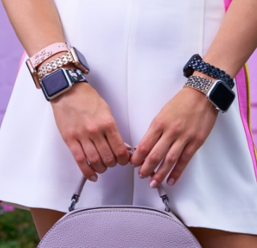 Stylish woman wearing multiple Kate Spade bands for Apple watch in various colorful leather prints and scalloped stainless steel bracelets.