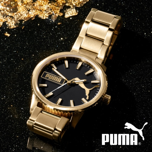 Gold-tone PUMA watch with black dial.