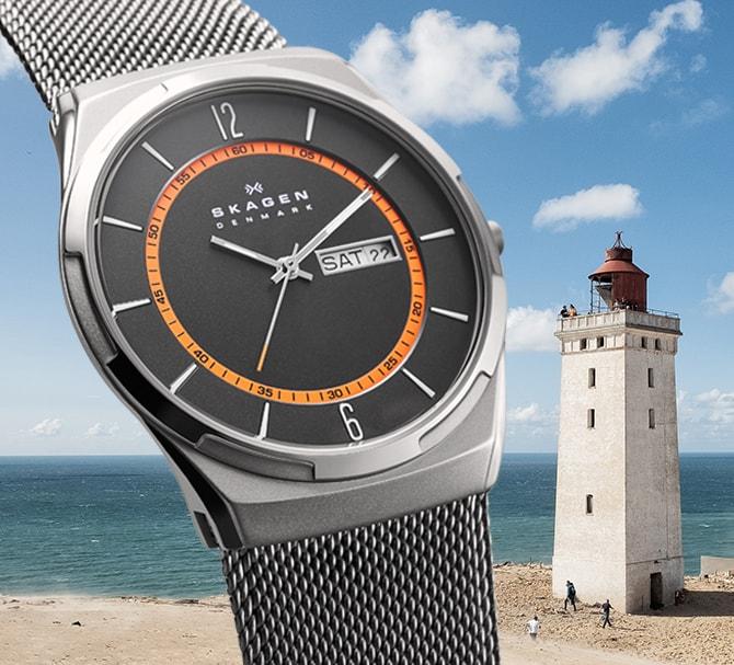 Deux montres Melbye de Skagen en bronze industriel pour hommes; une avec l'intérieur de chiffres pour le suivi des secondes bleu et une avec l'intérieur de chiffres pour le suivi des secondes orange