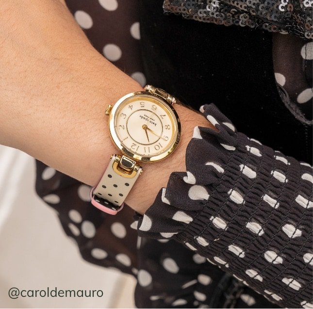 Woman wearing kate spade new york watch featuring polka dot-print.