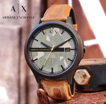 Armani Exchange watch featuring a camo-pring dial with repeating Arman Exchange text logos, yellow second hand, burnished tan leather strap in an industrial setting.